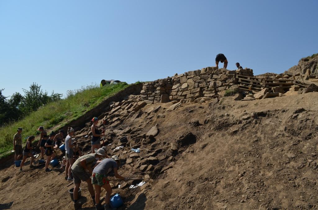 Badania wykopaliskowe na przedpolu fortyfikacji z wczesnej epoki brązu, w tle odbudowa bramy wschodniej badanej w 2015 roku (fot. J. Jędrysik)